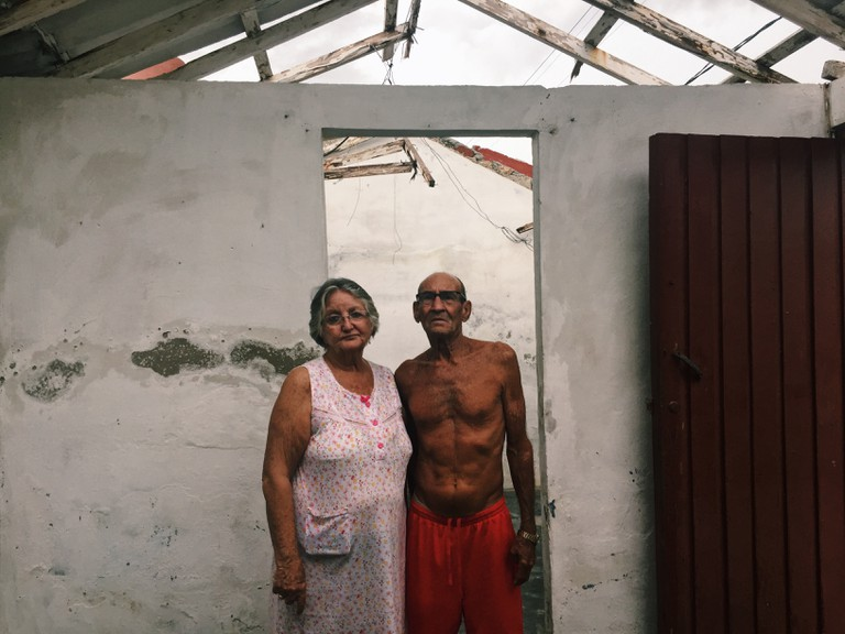 Gladys, 65 years old and Julian, 72 years old in Caibarién, Cuba, working to restore their home, which faces the sea.