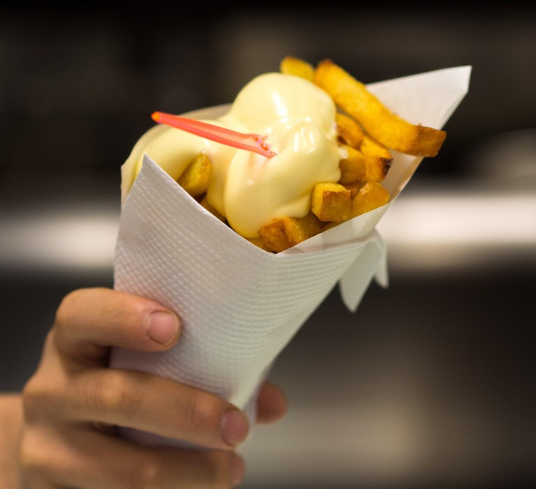 A cone of fries topped with fritessaus