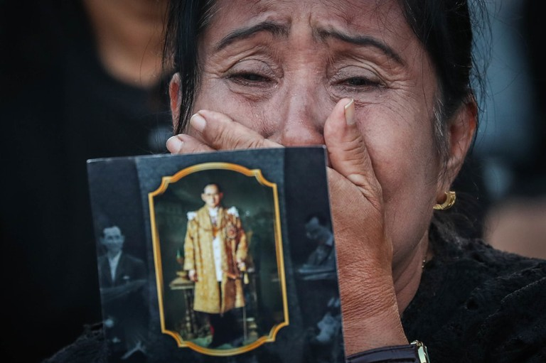 A Thai woman grieves while holding an image of the late king