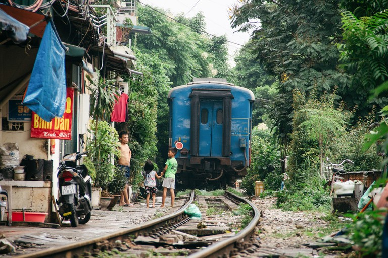 The train disappears and street life returns