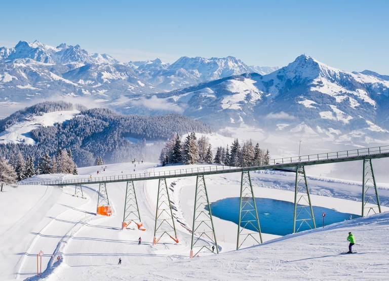 Ski train trail and small lake over Austrian alps