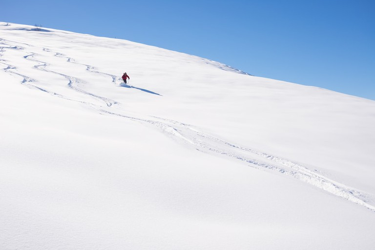 Skiing downhills off piste on snowy slope in the italian Alps