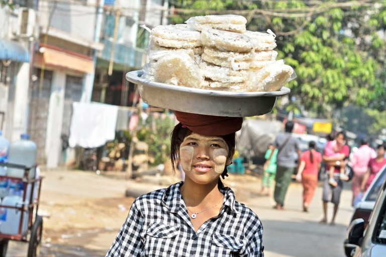 A woman carries goods to sell on her head in Yangon