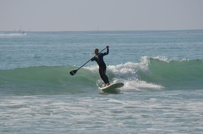 Catching a wave while stand-up paddling