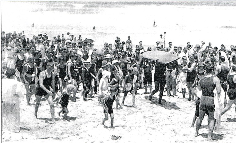 Duke carrying board up beach, 1915