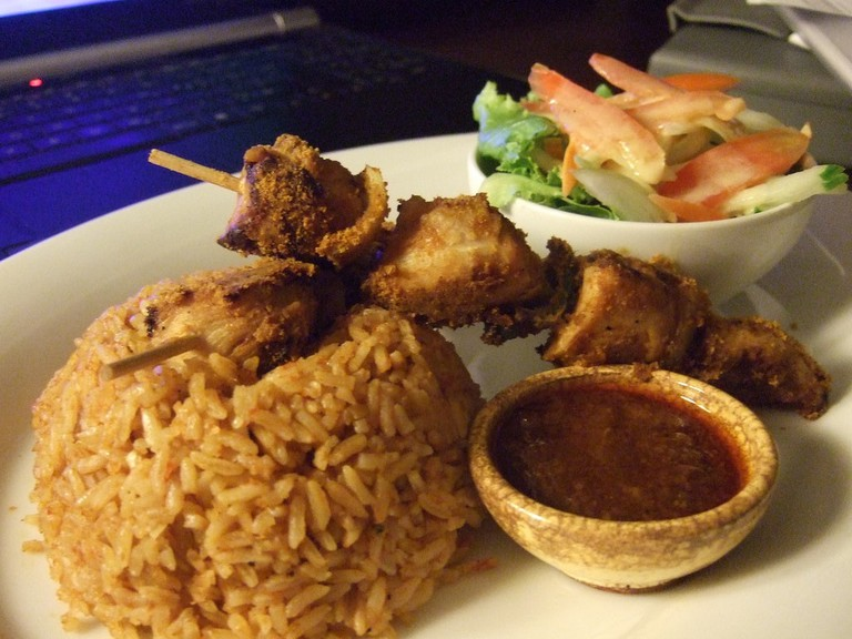 Jollof served with a chicken kebab and pepper dip