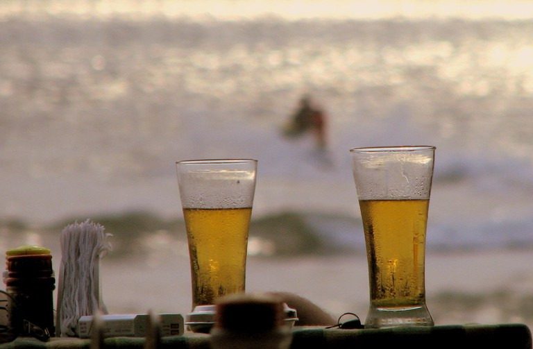 An outdoor table with mugs of beer overlooking the beach in Goa