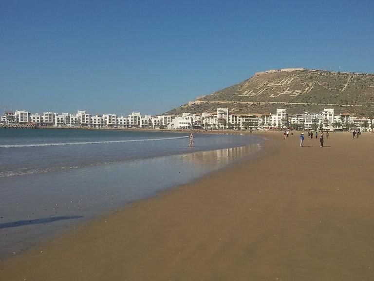 Sandy beach of Agadir with the hill of Agadir Oufella in the background
