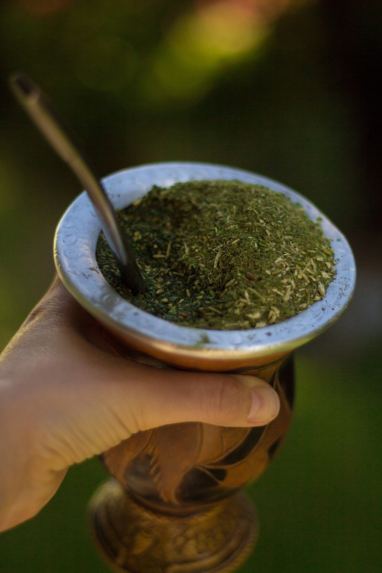 A hand holding a full mate cup with a straw