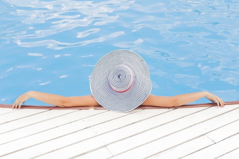 A woman wearing a hat lounging in the pool
