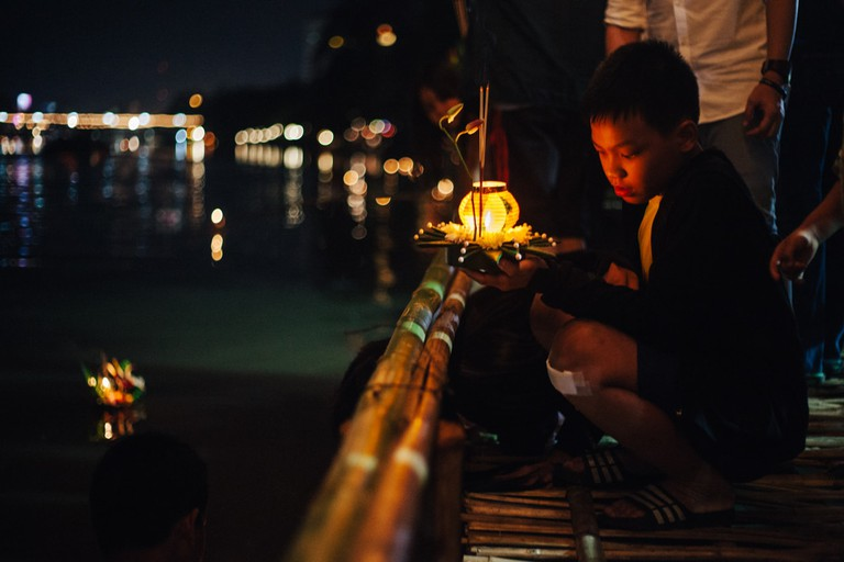 A boy prepares his krathong to float on the river
