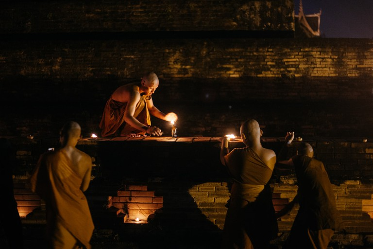 Monks light candles on an ancient stupa