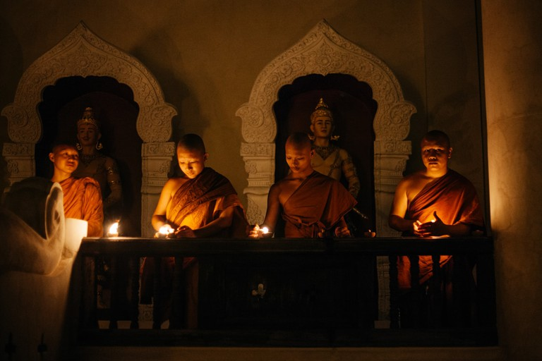 Four monks light candles outside a temple