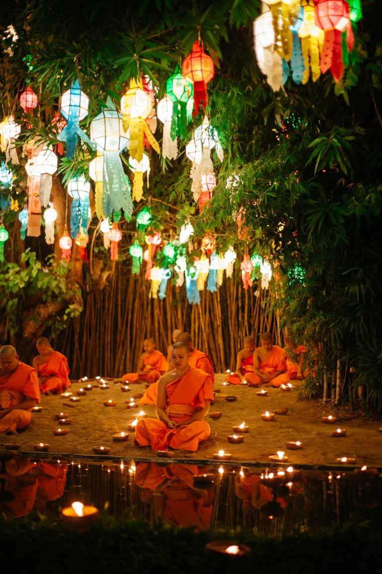 Monks sit and meditate surrounded by candles