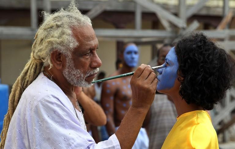 Renowned Cuban artist Manuel Mendive painting for a performance art piece