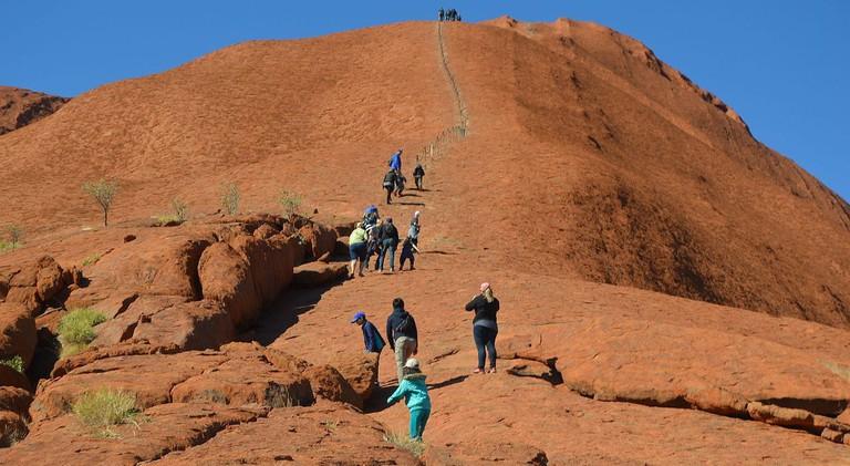 Tourists climb Uluru