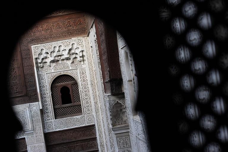 Peering through a keyhole in Bou Inania Madrasa, Meknes