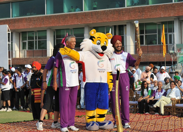 Milkha Singh (R) holding the Queen's Baton in the 2010 Delhi Commonwealth Games