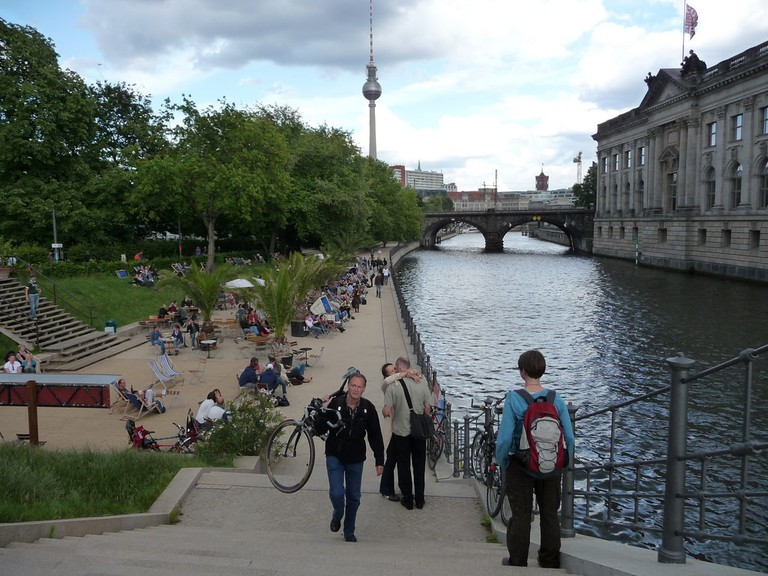 People relaxing and drinking by the Spree River, Berlin