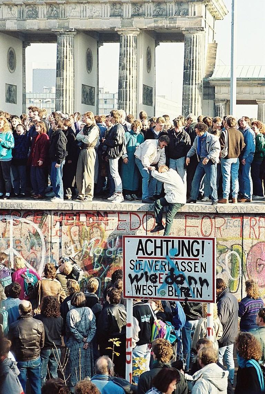 People atop the Berlin Wall near the Brandenburg Gate on November, 9 1989