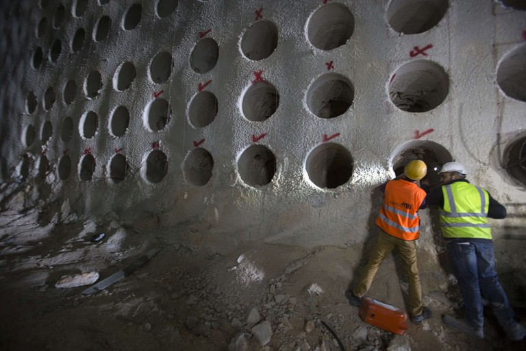 Workers looking inside one of the burial shafts