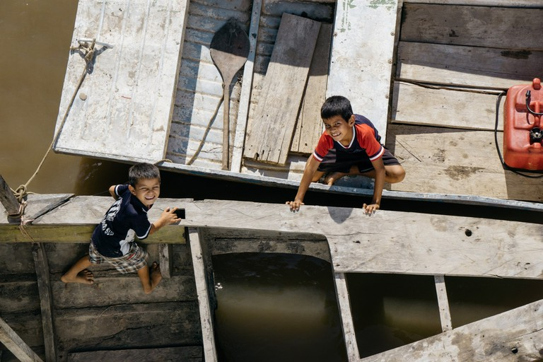 Two young children look up from below a cargo ship embarking on a three day journey down the Amazon