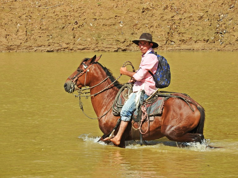 Crossing a river on horseback in the Plains