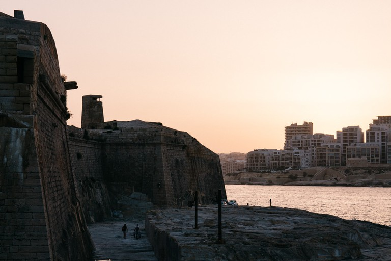A couple walks along the river as the sunsets in Valletta