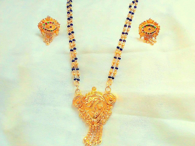 Mangalsutra along with a pair of matching earrings worn as jewelry