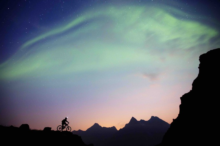 Mountain biking under the northern lights in Lofoten