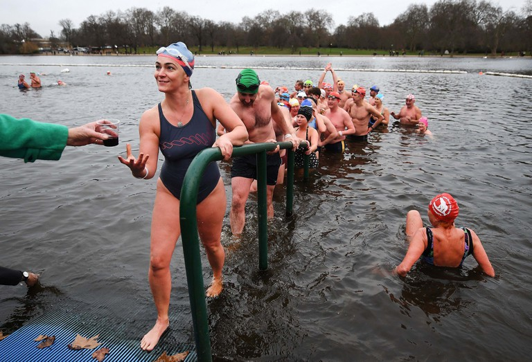 Mandatory Credit: Photo by ANDY RAIN/EPA/REX/Shutterstock (7665854m) Swimmers emerge from Serpentine Lake in Hyde Park following the annual Peter Pan Cup, an annual Christmas Day swim in London, Britain, 25 December 2016. The event, which has run every Christmas since 1864, sees outdoor swimming enthusiasts from the Serpentine Swimming Club dive into the chilly lido to see who can be first to swim 100 meters. The waters usually drop below 4C (40F) degrees in the winter, so swimmers need to be acclimatized to the freezing temperatures before participating in the race. The Peter Pan Cup is only open to members of the Serpentine Swimming Club who have qualified during the season. Swimmers enjoy mild weather for the annual Christmas Day swim in Hyde park, London, United Kingdom - 25 Dec 2016