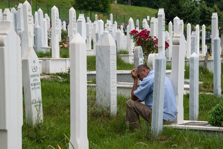 An unidentified man visits a grave in Sarajevo. More than 2.500 war victims (1992-1993) are buried in this cemetery   © dinosmichail/Shutterstock