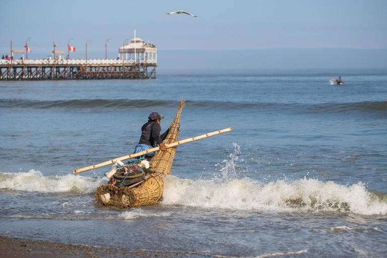 Fisherman enters the sea in Huanchaco, Peru