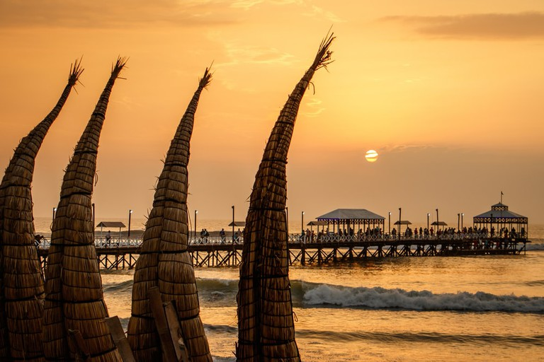 The sunset with traditional boat craft at Huanchaco town, near Trujillo, Peru