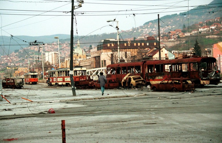 A man braves sniper fire to cross a no-mans land in the besieged Bosnian capital on Apr 4, 1993 in Sarajevo   © Northfoto/Shutterstock