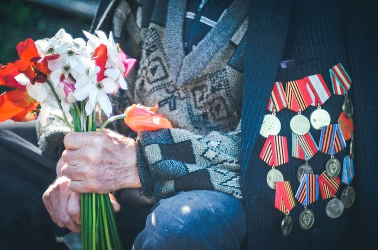 A veteran with several medals holding flowers