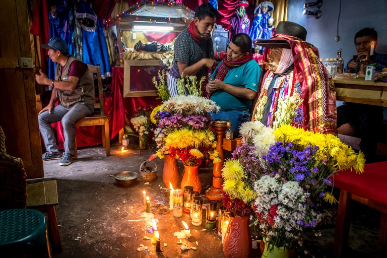 Followers of Maximon leave offerings for the deity in Santiago Atitlan, Guatemala