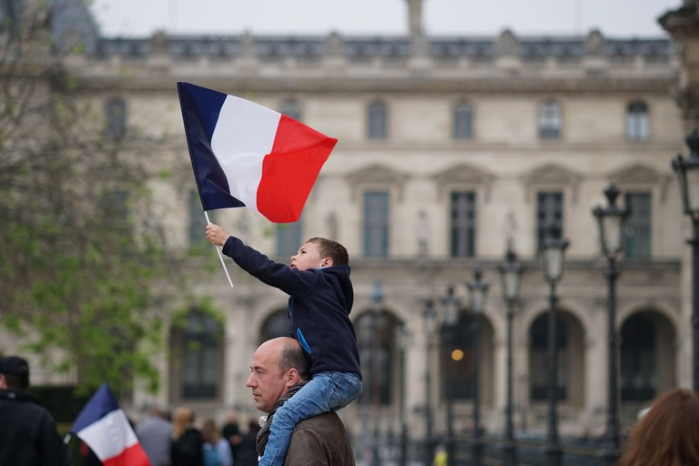 A child bears a French flag