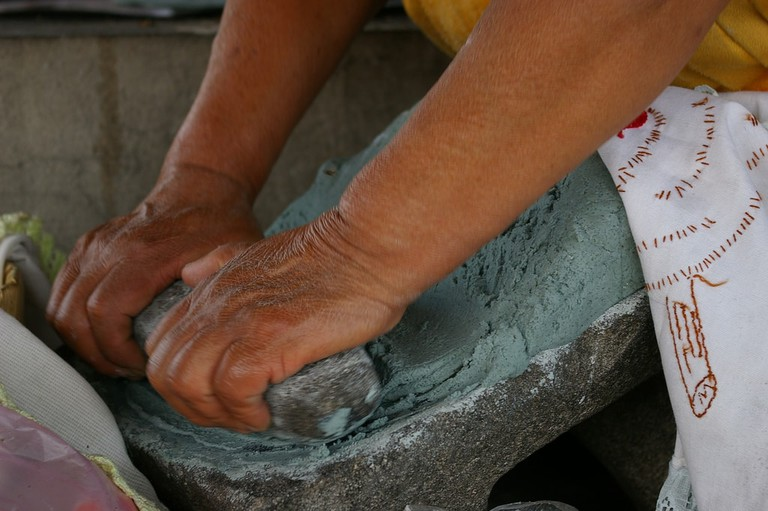Woman grinding corn for tortillas│
