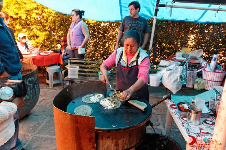 Woman making quesadillas on a comal │