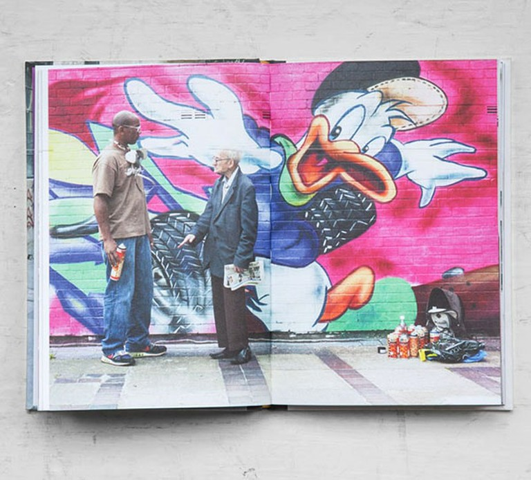 Joseph standing in front of graffiti with an artist in I've Lived in East London for 86 ½ Years by Martin Usborne, published by Hoxton Mini Press, £12.95