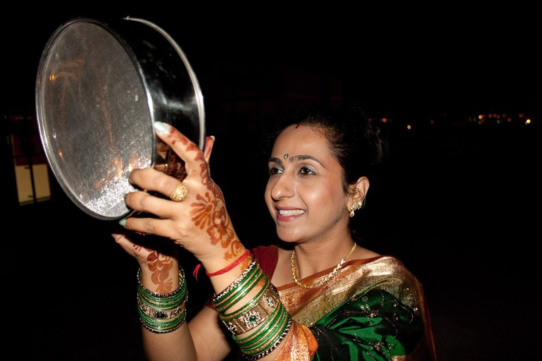 A married Hindu woman looking at the moon through a sieve on Karva Chauth