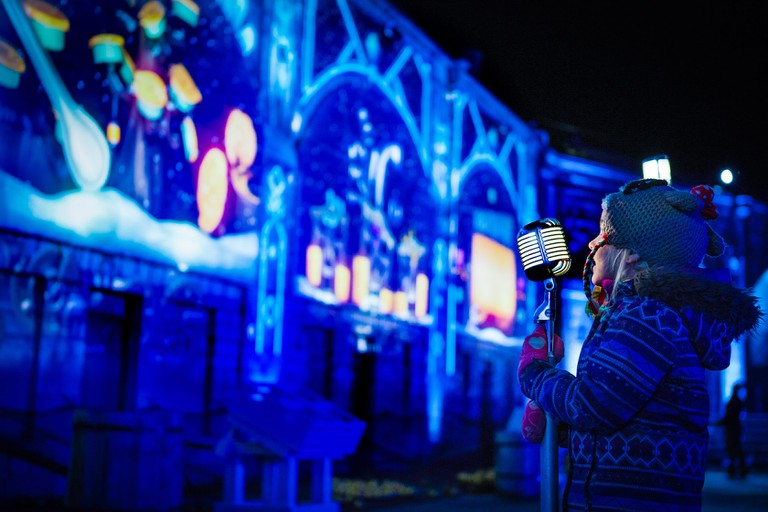 A young girl singing in the illuminated experience, Lumina Borealis at Fort Henry