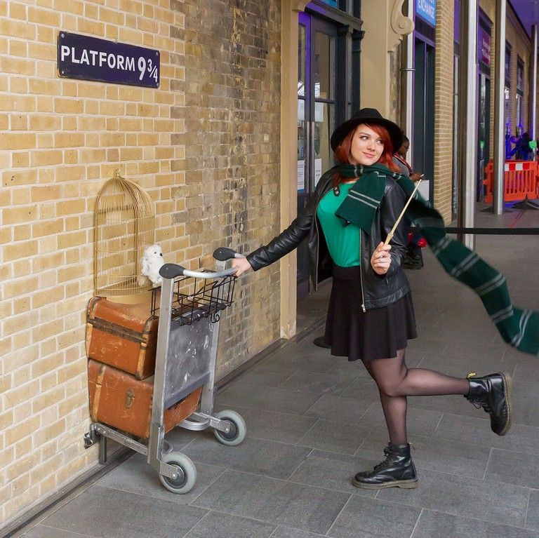 A Potter fan has her picture taken on the way to Platform 9 and 3/4
