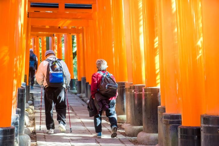 Elderly couple walking through the Red Torii Gate at Fushimi Inari Shrine in Kyoto, Japan
