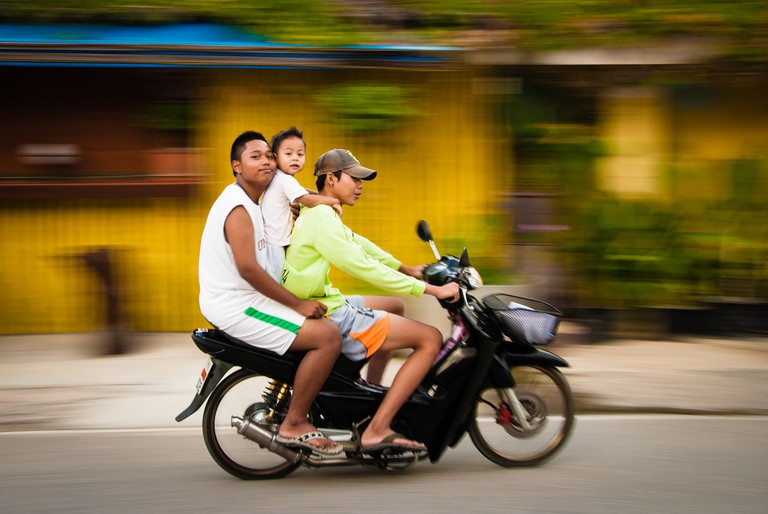 """<a href=""""https://www.flickr.com/photos/didierbaertschiger/8343851126/"""" rel=""""noopener"""" target=""""_blank"""">Thai family on a scooter"""