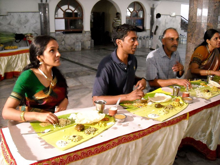 A_thali_served_on_banana_leaf_during_a_wedding,_south_India