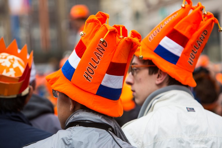 People celebrating annual King's Day in the old town of Amsterdam