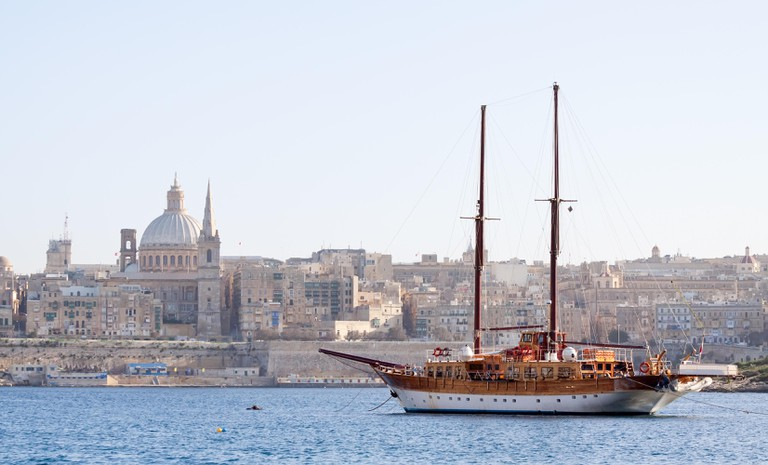 Vintage ship docked in creek against old town (Valletta, Malta)