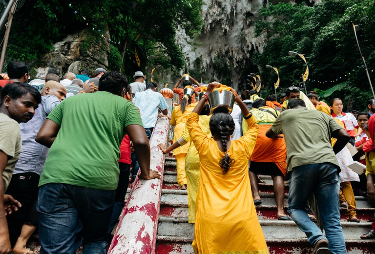 More devotees are seen carrying their pots of milk while ascending the steps